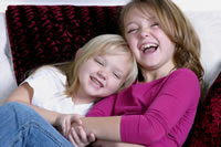 Two cheeky girls laughing